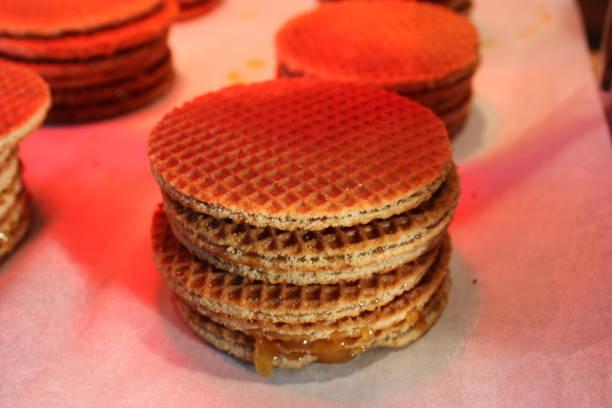stroopwafel, typisch holländisch süß. kekse, die in einer reihe angeordnet sind, die übereinander gestapelt sind. weißer hintergrund, rötliches licht - zimt waffeln stock-fotos und bilder