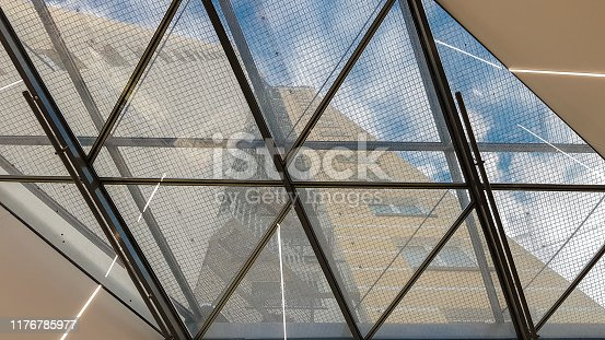 istock Structural glazing of the facade. Abstract background with glass ceiling elements in a modern building. view of the blue sky through a glass window, separated by lattice elements 1176785977