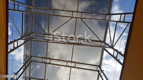 istock Structural glazing of the facade. Abstract background with glass ceiling elements in a modern building. view of the blue sky through a glass window, separated by lattice elements 1176786084