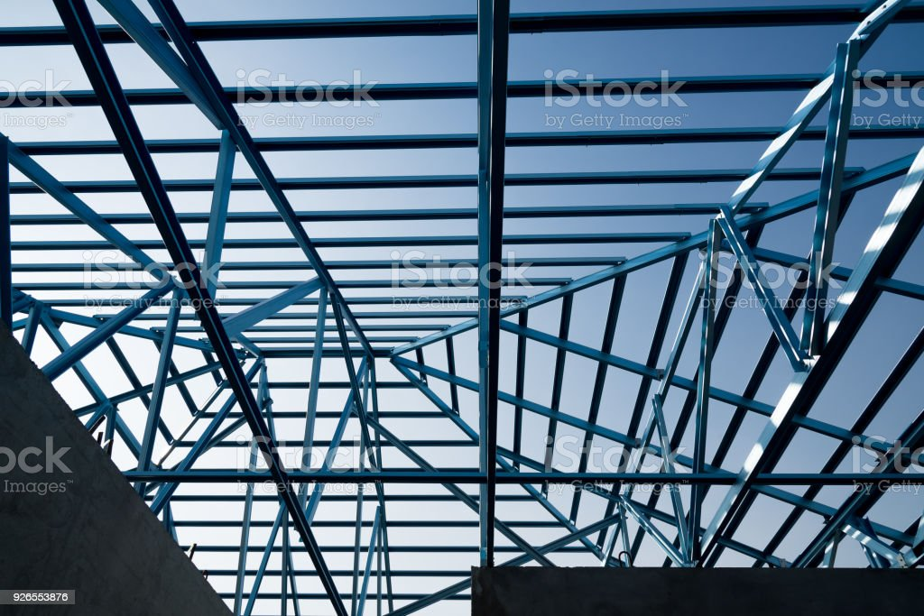 Structure of steel roof frame for building construction isolated on blue sky background. stock photo