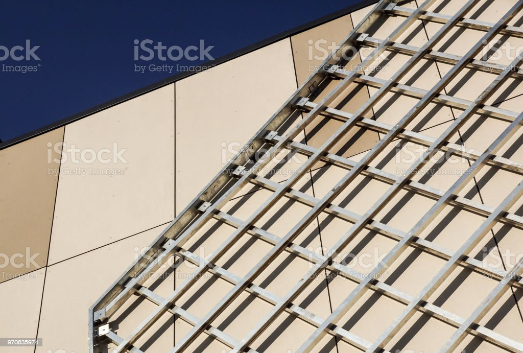 Structure of steel roof frame for building construction on sky background. stock photo