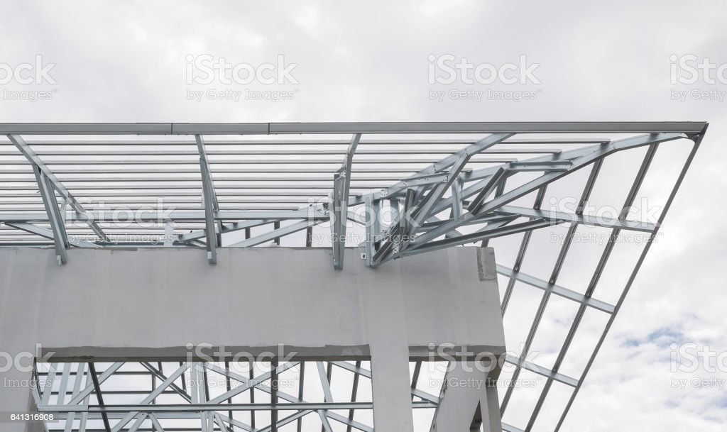 Structure of steel roof frame with blue sky and clouds at construction site stock photo