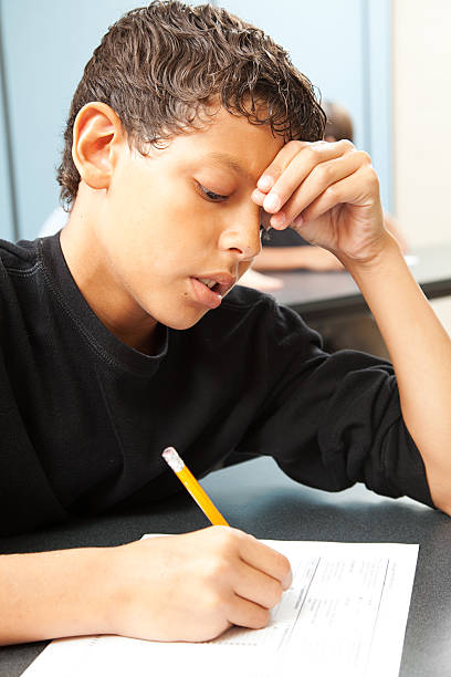 Struggling School Boy Handsome school boy struggling to finish a test in class. illiteracy stock pictures, royalty-free photos & images