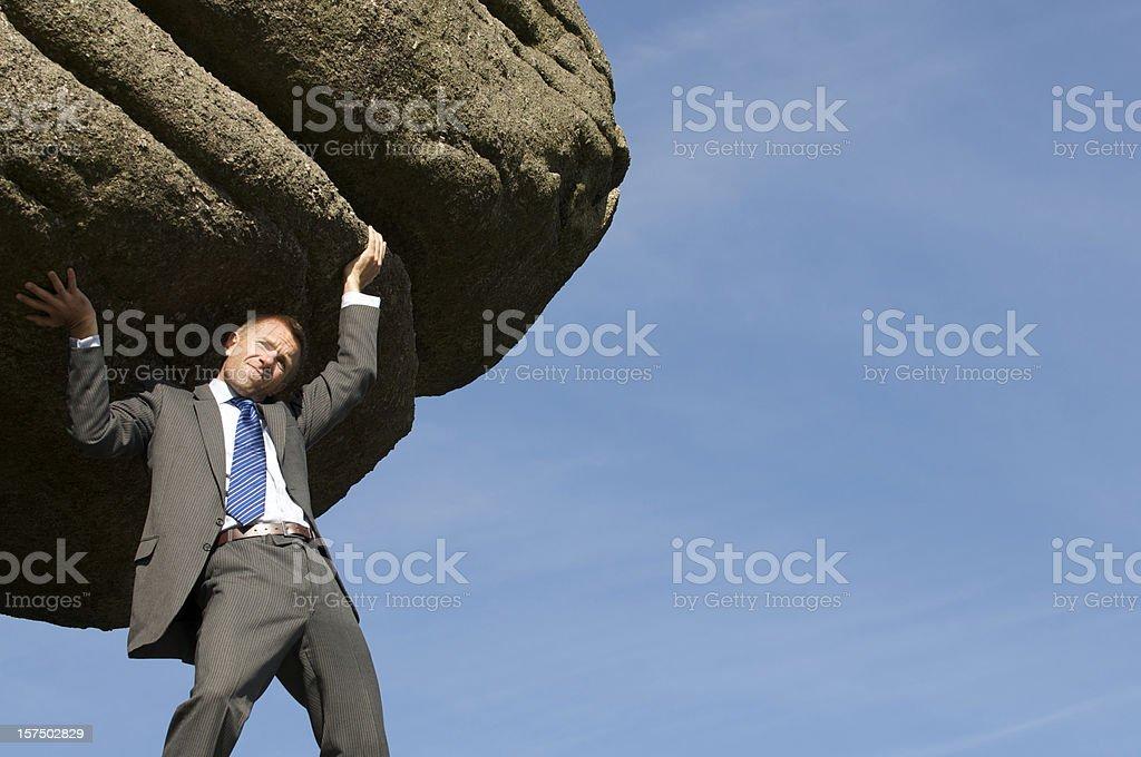 Struggling Strong Businessman Holding Huge Rock Boulder into the Sky stock photo