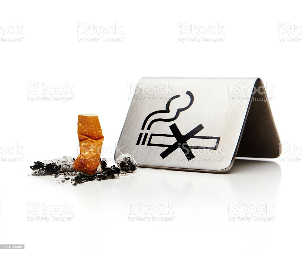 Stubbed out cigarette butt next to metal no smoking sign stock photo