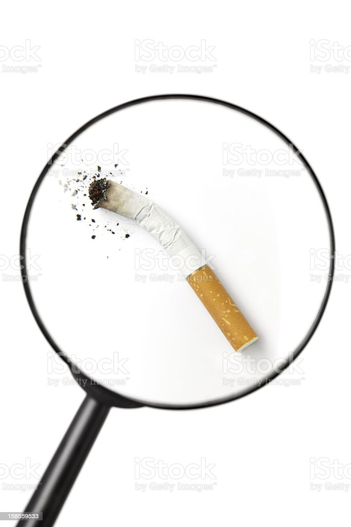 stubbed out cigarette viewed through magnifying glass stock photo