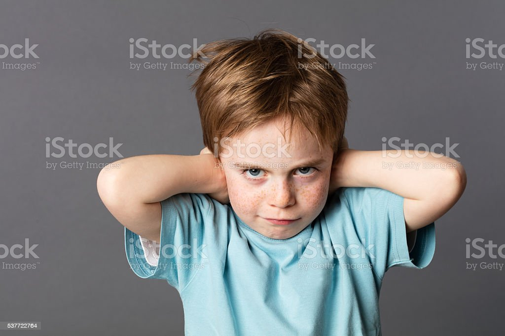 stubborn young kid teasing, covering closed ears, ignoring parents stock photo