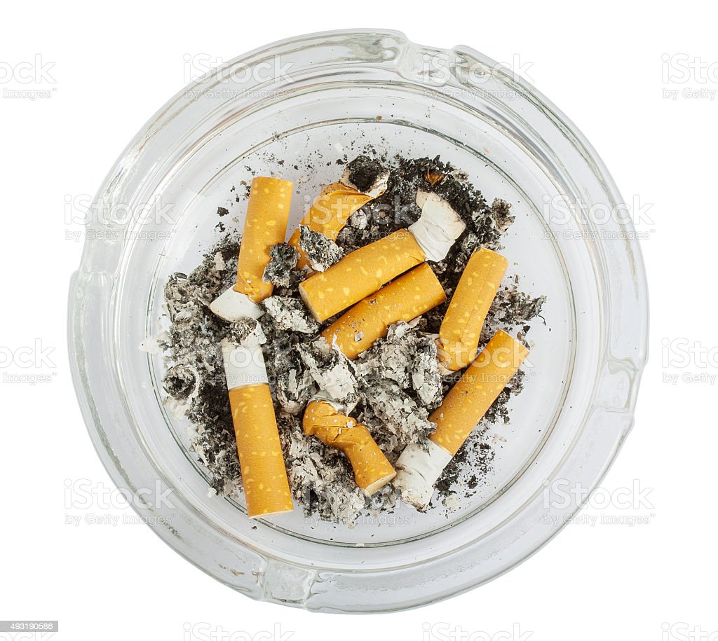 Stubs in glass ashtray top view stock photo