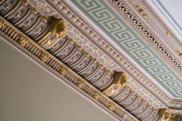 Stuck und luxuriöse Dekorationselemente an der Decke. Luxus-Ästhetik in einem Wohnhaus Dekor. Goldene Löwenkopfstücke an der Decke – Foto