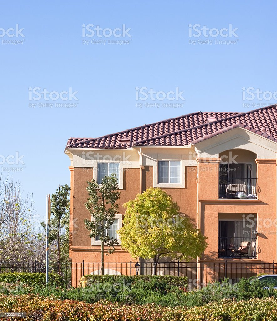 Stucco Apartment Building Exterior and Blue Sky royalty-free stock photo