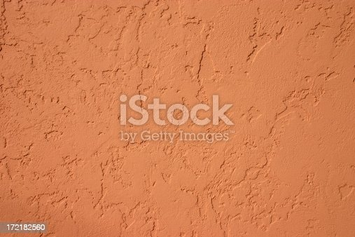 Terra cotta colored stucco surface. Textured surface. Adobe wall.