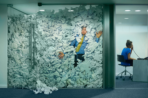 A businessman is trapped in his glass office by a surplus of discarded ideas on paper . His colleague in the next office is working more efficiently and is oblivious to him being trapped .