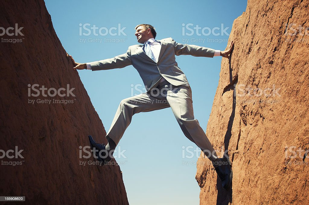 Stuck Businessman Standing Outdoors Wedged between Two Rock Walls royalty-free stock photo