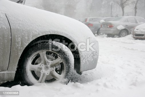 close up shot of frozen car tire during snow storm.
