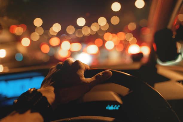 coincé dans les embouteillages, main gauche sur le volant - voiture nuit photos et images de collection
