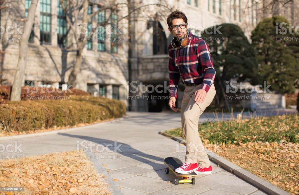 A Student about to Ride a Skateboard Towards Direction of Path. stock photo