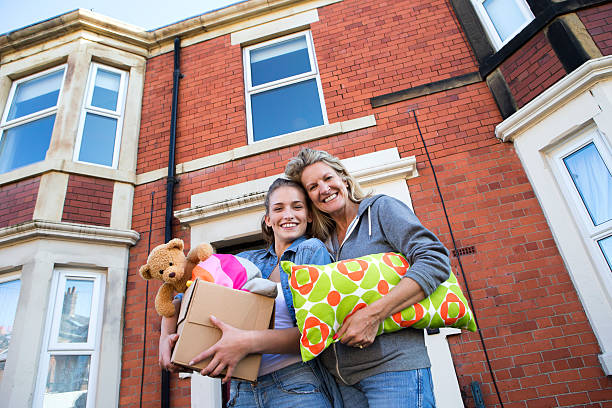 student accommodation - happy mom packing some toys stock photos and pictures