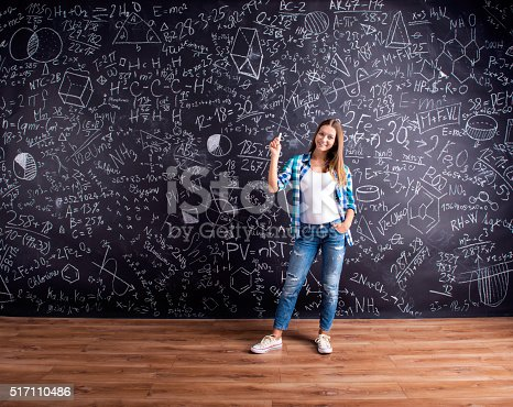 istock Student against a big blackboard with mathematical symbols 517110486
