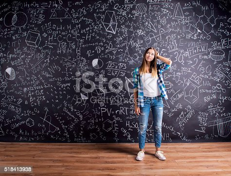 istock Student against a big blackboard with mathematical symbols 518413938