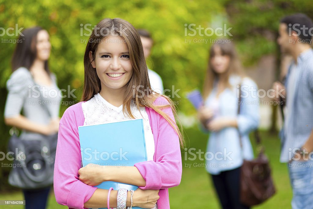 Student amidst peers smiling at camera with a folder stock photo