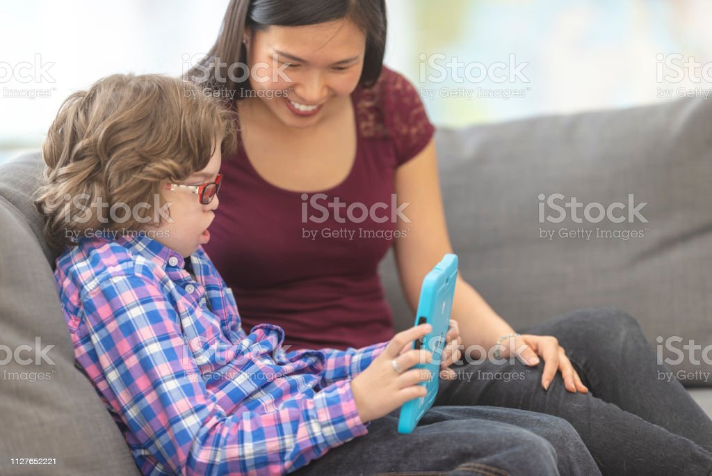 Student and his tutor using a tablet together stock photo