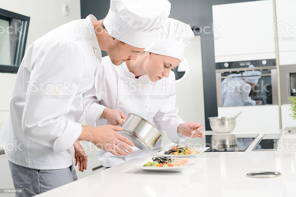 student and teacher in professional cook school kitchen preparing dish stock photo