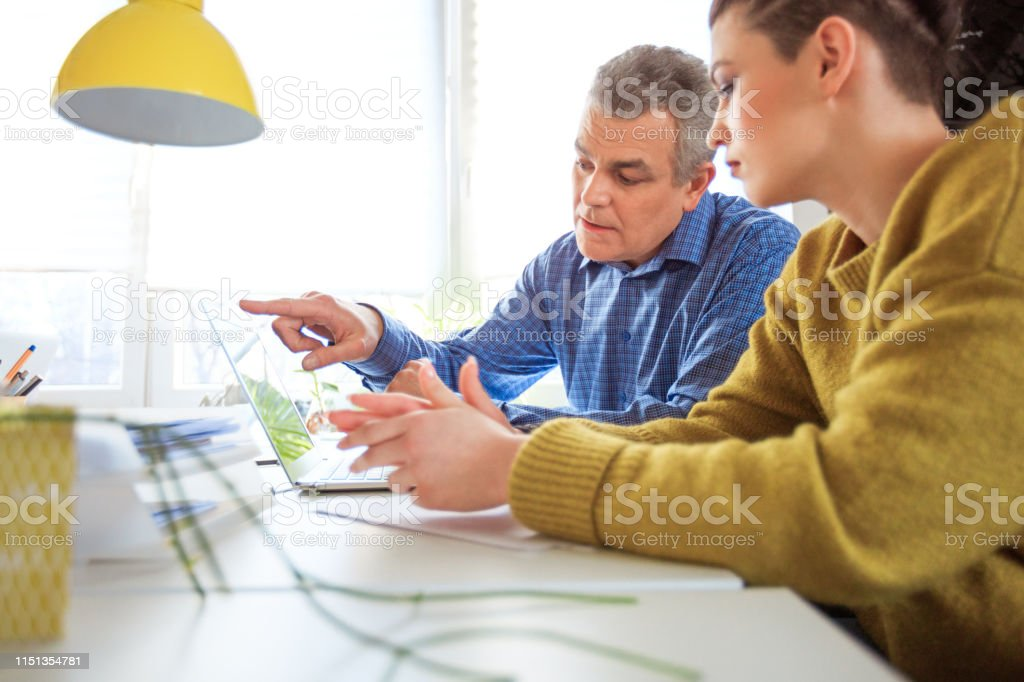 Student and therapist looking at laptop in meeting Student and therapist looking at laptop in university. Young woman and mature professional are having meeting at desk. They are in mental health therapy. 18-19 Years Stock Photo