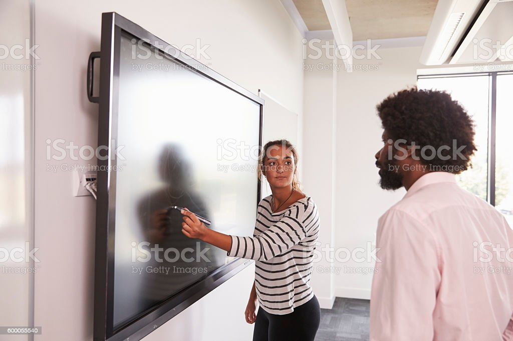 Student And Tutor Discuss Project On Interactive Whiteboard stock photo