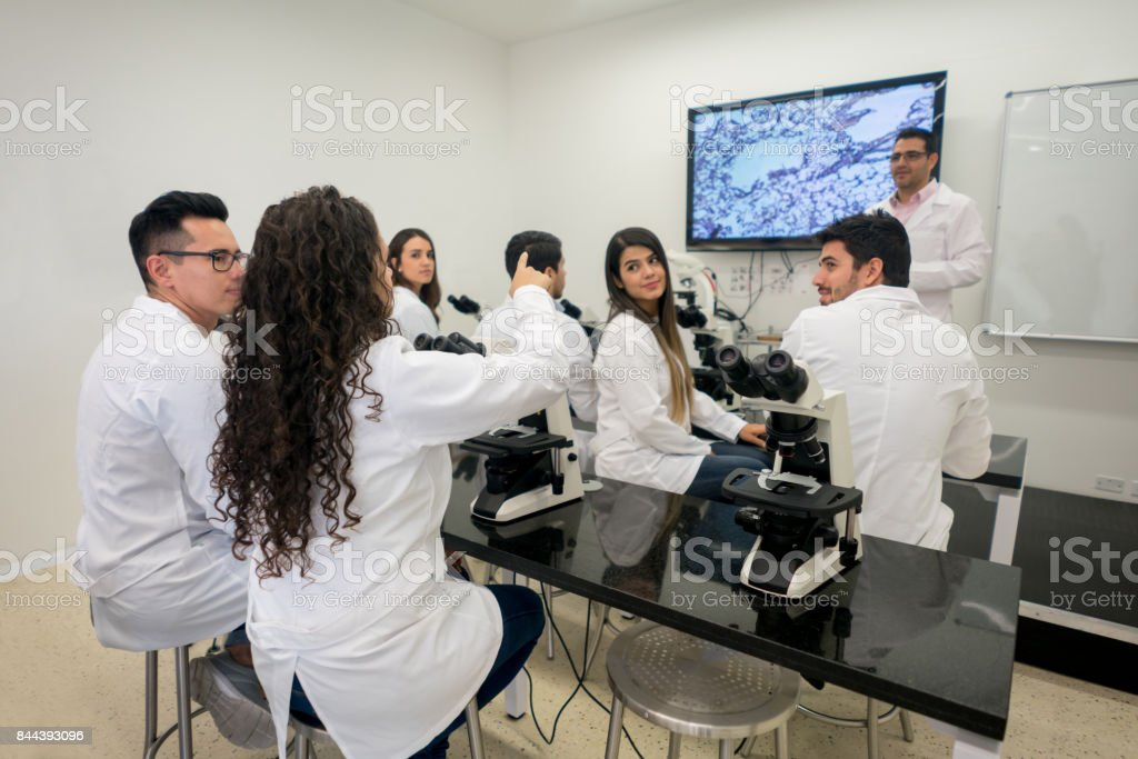 Student asking a question in science class at the university while...
