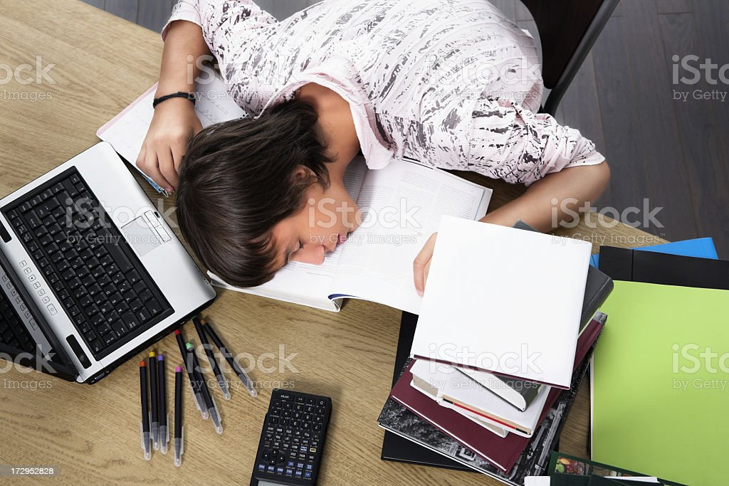 A student asleep on book with books laptop and supplies near stock photo