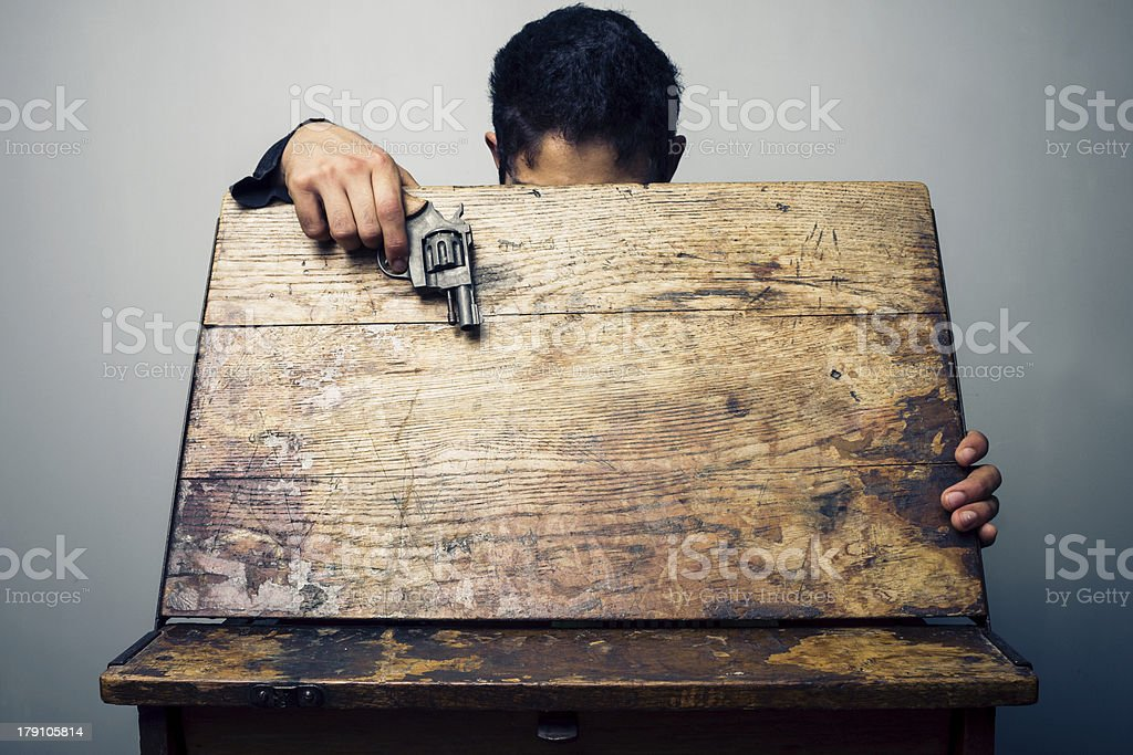 Student at school desk with gun stock photo