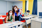 istock student at school wearing N95 Face masks 1253123011