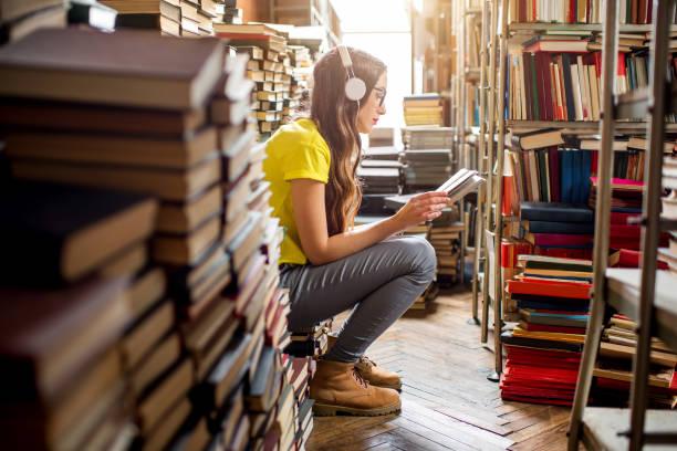 studentin in der bibliothek - geek t shirts stock-fotos und bilder