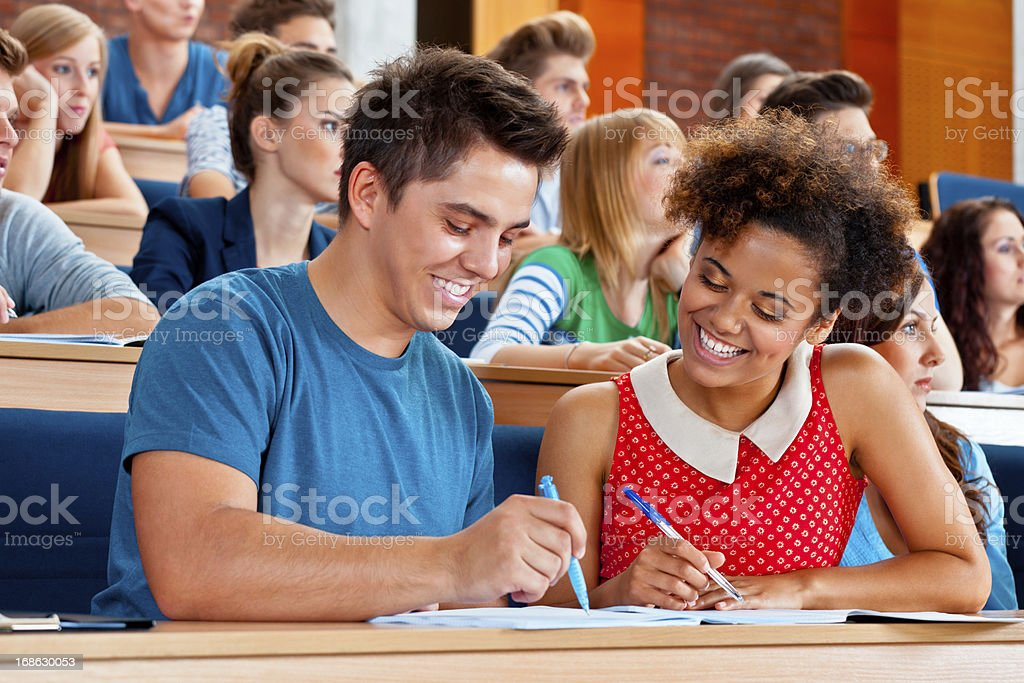 Student at the university Large group of students sitting in the lecture hall at university. Focus on the cheerful young man and woman working together. 20-24 Years Stock Photo