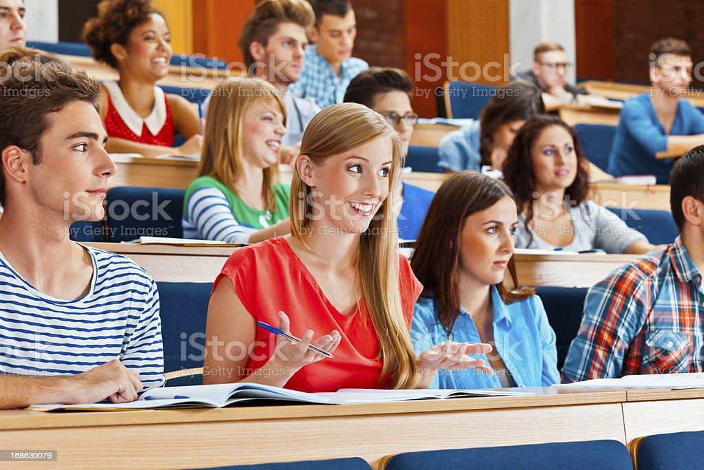 Student at the university Large group of students sitting in the lecture hall at university. Focus on the young woman answering question. 20-24 Years Stock Photo