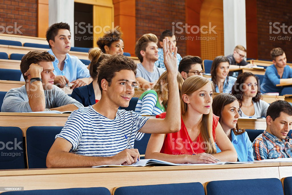 Student at the university Large group of students sitting in the lecture hall at university. Focus on the young man raising hand to answering question. 20-24 Years Stock Photo