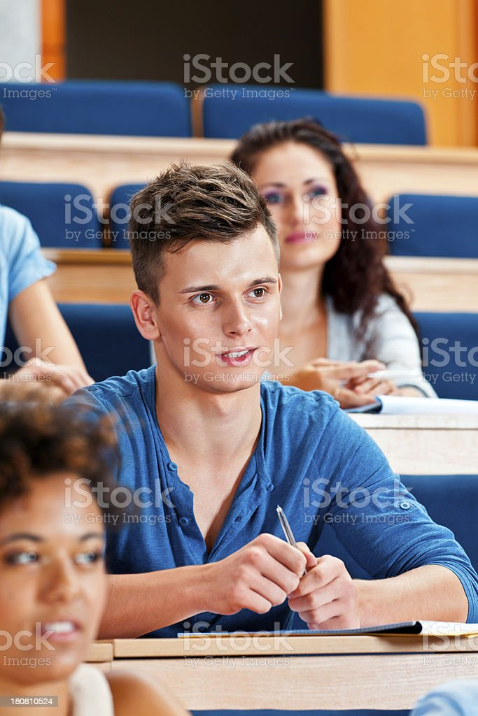 Student at the university College students sitting in the lecture hall at the university and listening to the lecture. Focus on the young man. 20-24 Years Stock Photo