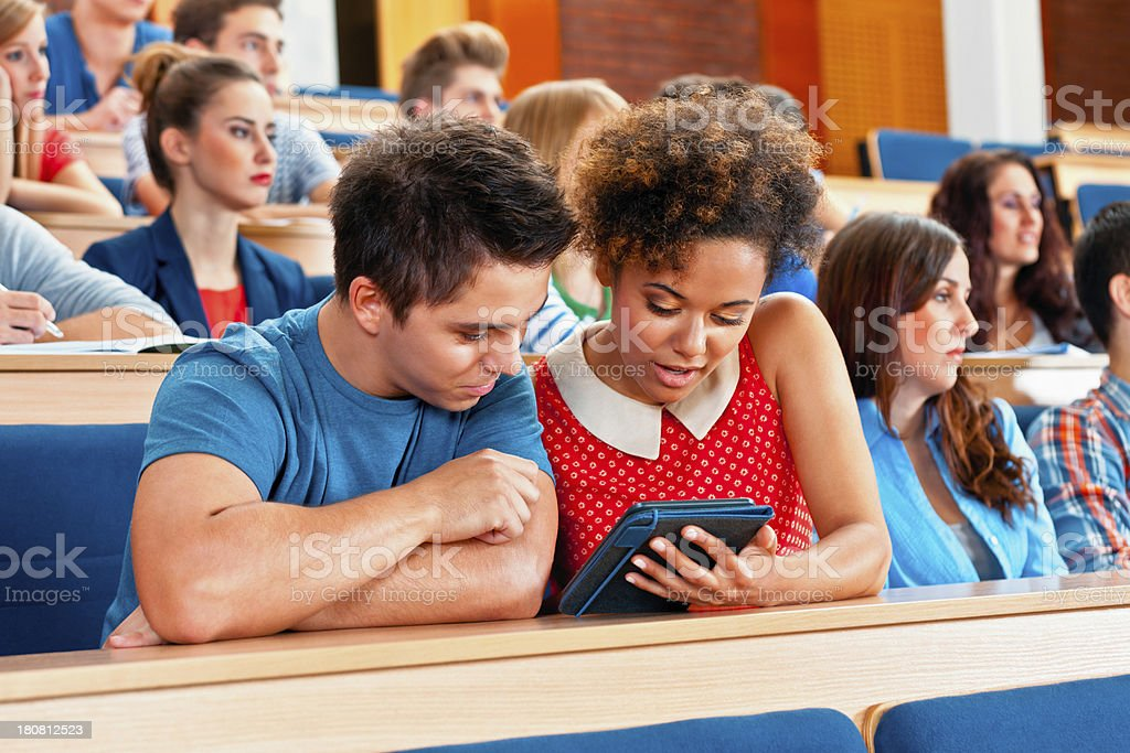 Student at the university Large group of students sitting in the lecture hall at university. Focus on the young woman and man using an e-reader together. 20-24 Years Stock Photo