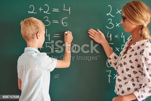 istock Student boy with chalk next to the chalkboard 638742538