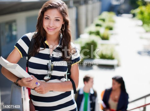 istock Student carrying book on steps outdoors 143071403
