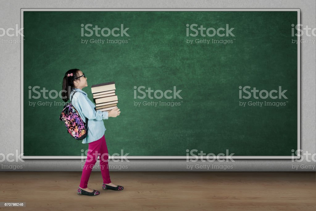 Student carrying pile of books in classroom stock photo
