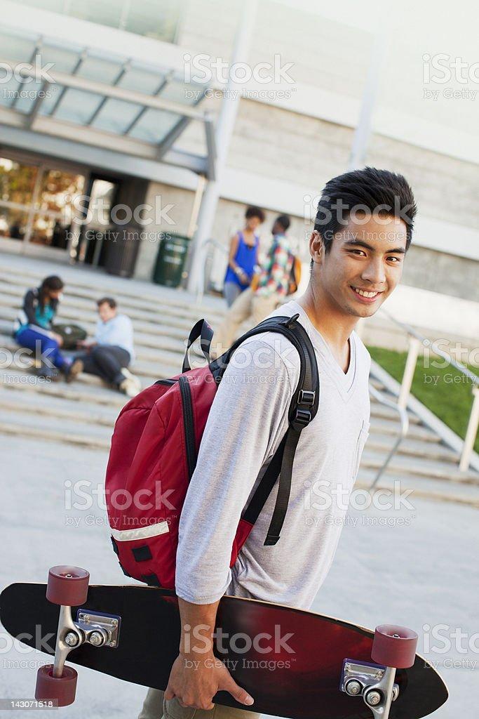 Estudante Carregando skate ao ar livre - foto de acervo