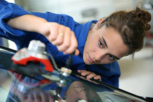 Student changing car windshield in auto shop stock photo