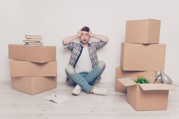 Student checkered casual shirt outfit space place people bad difficult concept. Exhausted frustrated going crazy guy touching head with hands crossed legs confused about the amount of belongings stock photo