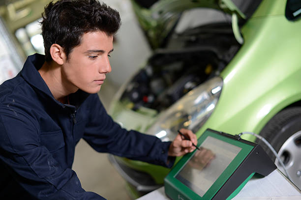 Student checking car with computer in garage stock photo