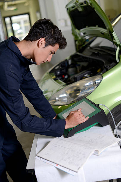 Student checking car with computer stock photo