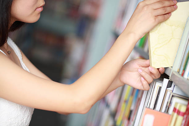 Student Choosing Book in Library stock photo