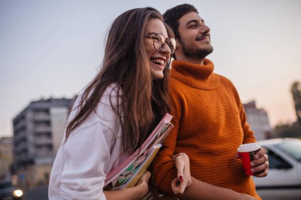 student couple having fun after campus - compagni scuola foto e immagini stock