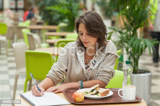 1183295518 istock photo Student doing homework while having breakfast in the cafe 846525182