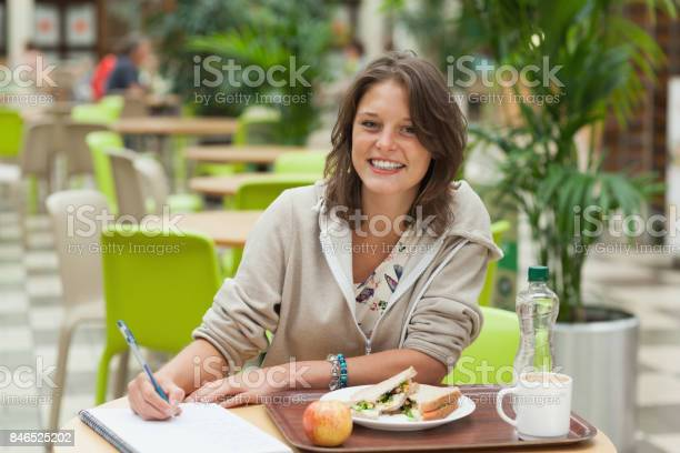 Student doing homework while having breakfast in the cafeteria picture id846525202?b=1&k=6&m=846525202&s=612x612&h=hsfxm3poltpuj238ilpulccl kxbai 2bgo5nac0y40=